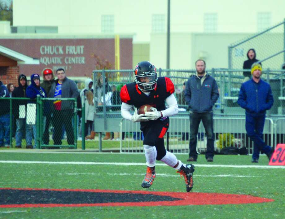 Edwardsville's Rodney Smith scoops up a punt from Minooka at the 47-yard line early in the first quarter of a Class 8A quarterfinal game on Nov. 11 inside the District 7 Sports Complex.