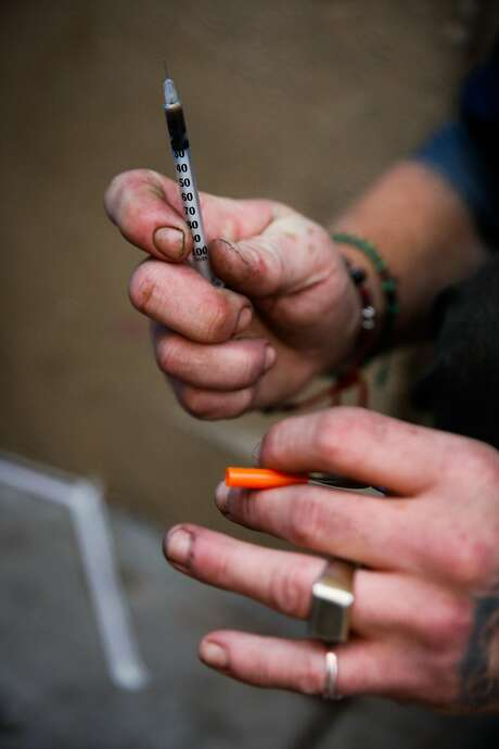 Top: The city shimmers, as viewed through the Golden Gate Bridge's cables from the Marin Headlands. Left: On Redwood Street near San Francisco's Civic Center, Spencer gets ready to give himself a shot of heroin. Photo: Gabrielle Lurie, The Chronicle