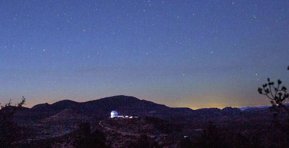 Looking in the direction of Balmorhea, stars appeared above the mountains and the Hobby-Eberly Telescope at the McDonald Observatory near Fort Davis, Texas on March 27, 2017. The view from the observatory now includes the glow from the Permian Basin oil field, incandescent with the work of 24-hour drilling, fracking and gas flaring. Photo: Carolyn Van Houten /San Antonio Express-News / 2017 San Antonio Express-News