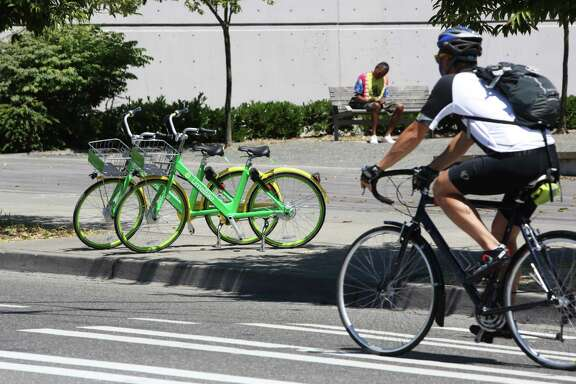 A Seattle bicyclist passes two LimeBike cycles in lower Queen Anne on July 26. LimeBike is one of six companies that offer dockless bike sharing considering launching in Houston.
