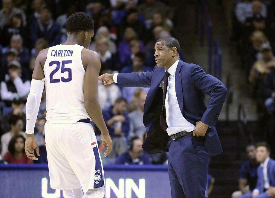 UConn head coach Kevin Ollie gives instruction to Josh Carlton against Colgate on Friday. Photo: Peter Casolino / Hartford Courant / Hartford Courant