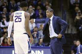 UConn head coach Kevin Ollie gives instruction to Josh Carlton against Colgate on Friday.