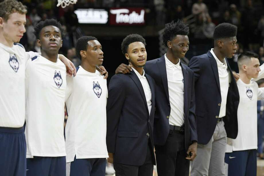 UConn's Jalen Adams, center, stands for the national anthem before Friday's game against Colgate. Adams was suspended after he was charged with a misdemeanor crash involving a scooter he was operating. Photo: Jessica Hill / Associated Press / AP2017