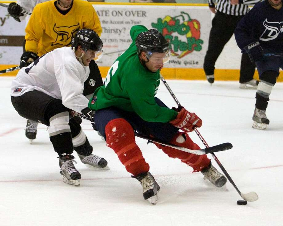 Andrew Willock, right, of the Green team gets inside the White team's Michael Jordon to score a goal during the Danbury Whalers' All-Star game which concluded the two-day tryout session Saturday night at the Danbury Arena. Photo: Barry Horn / The News-Times Freelance