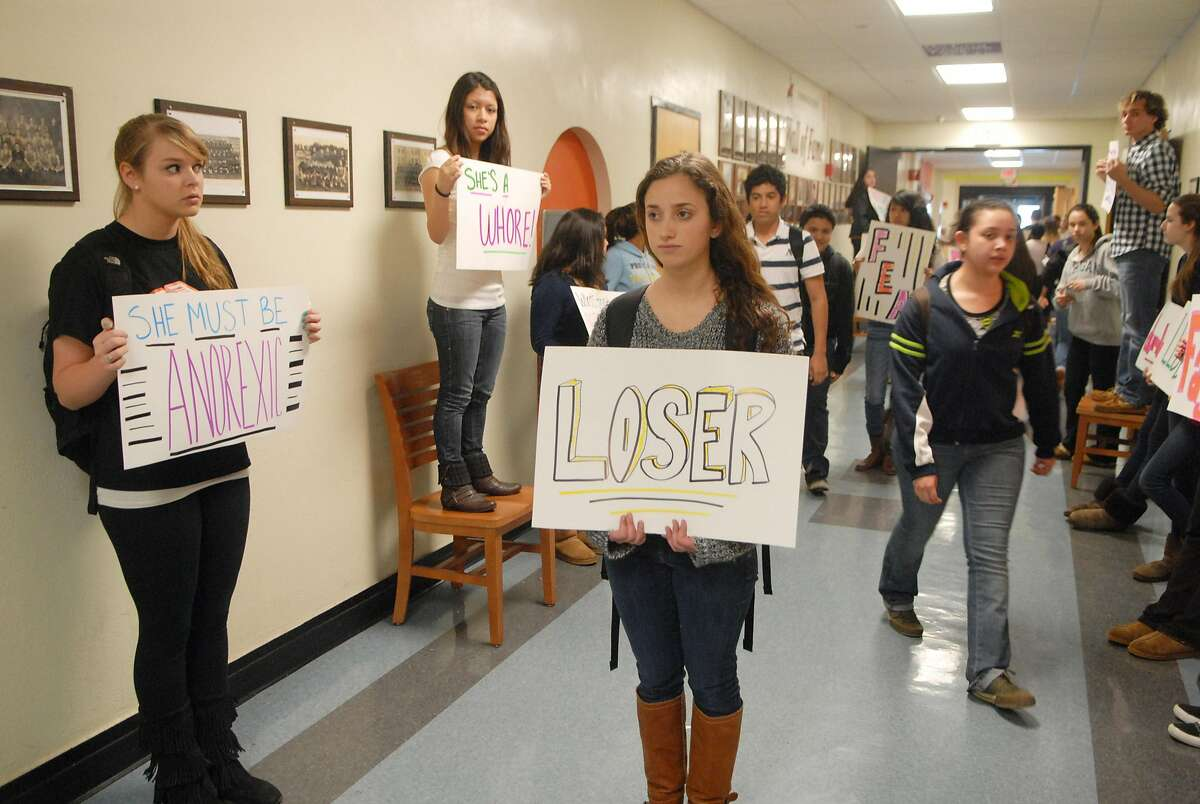 Stamford High School students Dylan Keith, Melissa Sigua (on chair) and Nicole Lorenti hold signs for Stop Hallway Harassment in Stamford, Conn. on Monday March 26, 2012, they are members of MYLC.