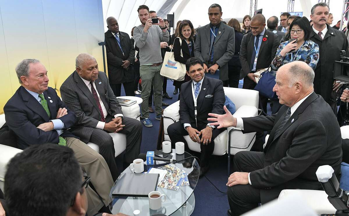 """Former New York Mayor and billionaire Michael Bloomberg, left, speaks with Fiji prime minister and COP president Frank Bainimarama, beside him, and California Governor Jerry Brown, right, in the U.S. Climate Action Center at the COP 23 Fiji UN Climate Change Conference in Bonn, Germany, Saturday, Nov. 11, 2017. Bloomberg's """"America's Pledge"""" campaign works to compile and tally the climate actions of states, cities, colleges, businesses, and other local actors across the entire U.S. economy. (AP Photo/Martin Meissner)"""