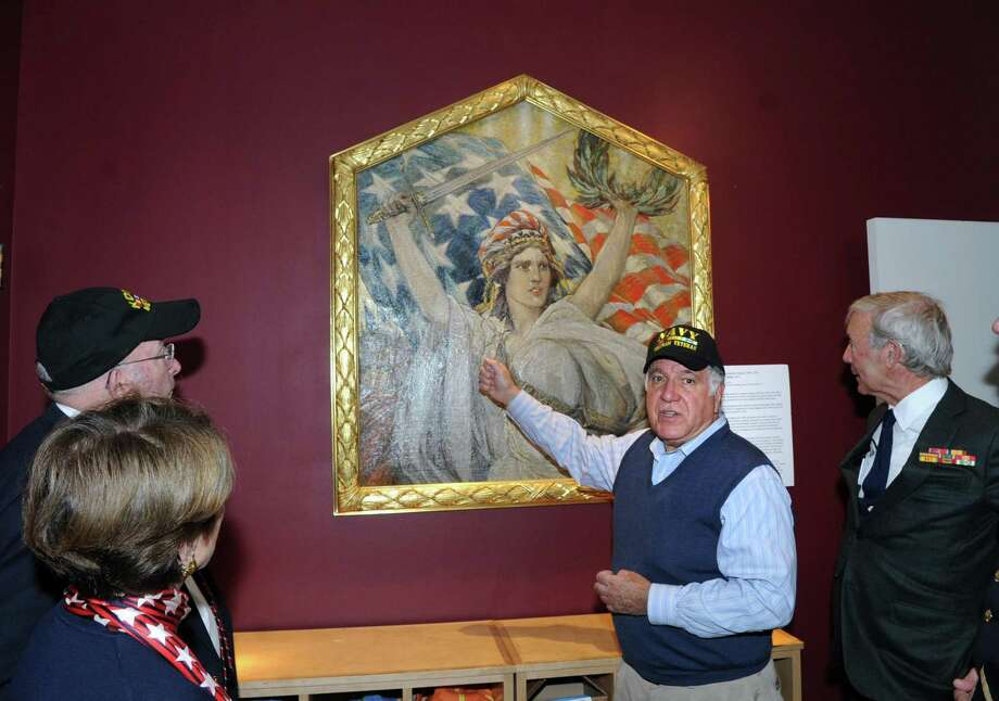 "Second from right, Greenwich resident Dean Gamanos, a Navy veteran, discusses the George Wharton Edwards oil on canvas 1918 painting, ""Miss Liberty,"" as part of the Greenwich Veterans Day activities at the Bruce Museum in Greenwich on Saturday. The painting belongs to American Legion Post 29 in Glenville and is temporarily on loan to the museum and can be seen in the museum's lobby area. Photo: Bob Luckey Jr. / Hearst Connecticut Media / Greenwich Time"