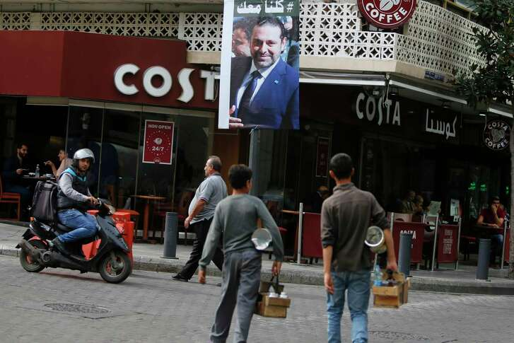A poster shows resigned Lebanese Prime Minister Saad Hariri, who said Monday he will return from Saudi Arabia to seek a settlement in his government.