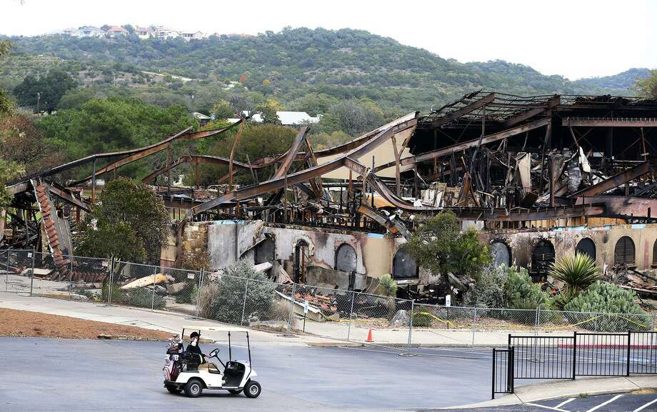 A man driving a golf cart passes the burned club house at the Tapatio Springs Hill Country resort near Boerne, Texas. A fire destroyed the building Saturday night November 4, 2017. Tapatio Springs is on 220 acres in the Hill Country. Its 18-hole golf course recently underwent a $2 million renovation. One of its owners is country music star George Strait. Photo: John Davenport, STAFF / San Antonio Express-News / ©John Davenport/San Antonio Express-News