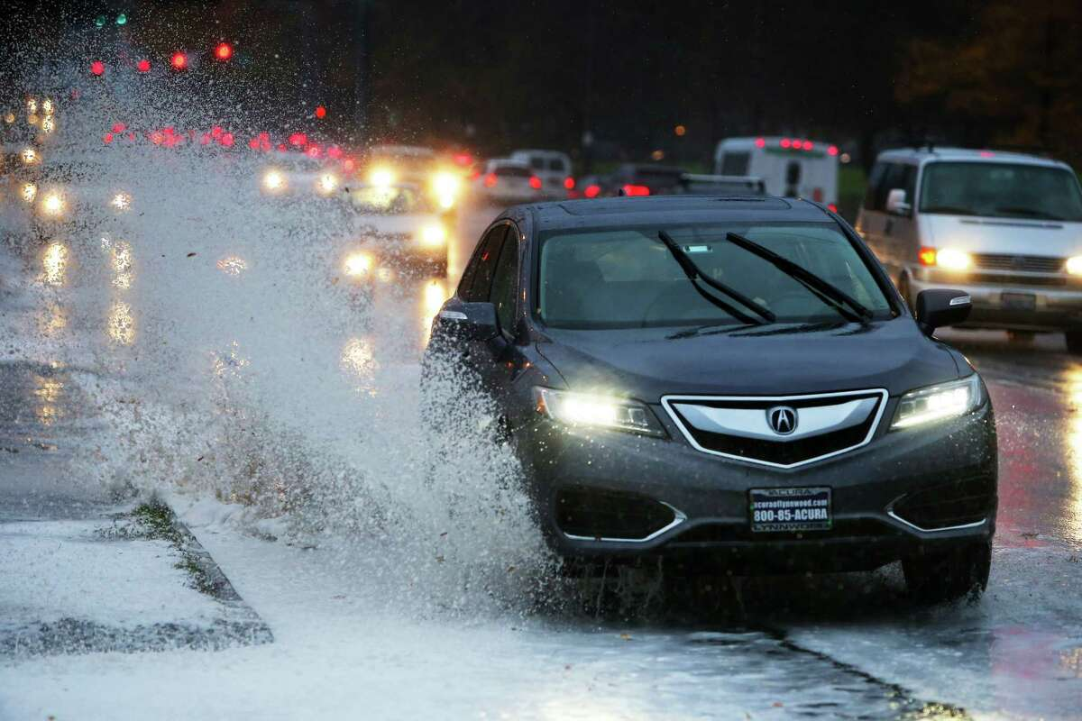 Cars drive through a puddle of frothy water in the University District as high winds and rain tear through the Seattle area Monday, Nov. 13, 2017.