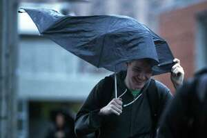 Students shield themselves from the elements on the 15th Avenue pedestrian bridge in the University District as high winds and rain tear through the Seattle area Monday, Nov. 13, 2017.