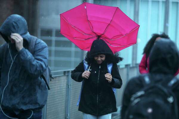 Students walk over the 15th Avenue pedestrian bridge in the University District as high winds and rain tear through the Seattle area Monday, Nov. 13, 2017.