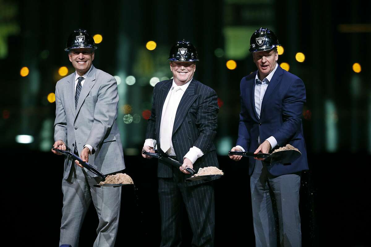 Oakland Raiders owner Mark Davis, center, poses for photographs beside Nevada Gov. Brian Sandoval, left, and NFL Commissioner Roger Godell during a ceremonial groundbreaking for the Raiders' stadium Monday, Nov. 13, 2017, in Las Vegas. After years of planning, dealing and getting millions in public financing approved, the team broke ground on a 65,000-seat domed stadium in Las Vegas, across the freeway from the city's world-famous casinos. (AP Photo/John Locher)