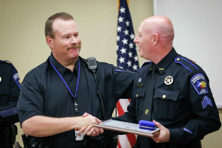 Precinct 1 Constable's deputy Brian Luly, right, shakes hands with then Panorama Village Police officer Billy Beavers, now Precinct 1 Constable's deputy, left, during a certificate of valor presentation on Monday at Precinct 1 Constable's Office. Photo: Michael Minasi, Staff Photographer / © 2017 Houston Chronicle