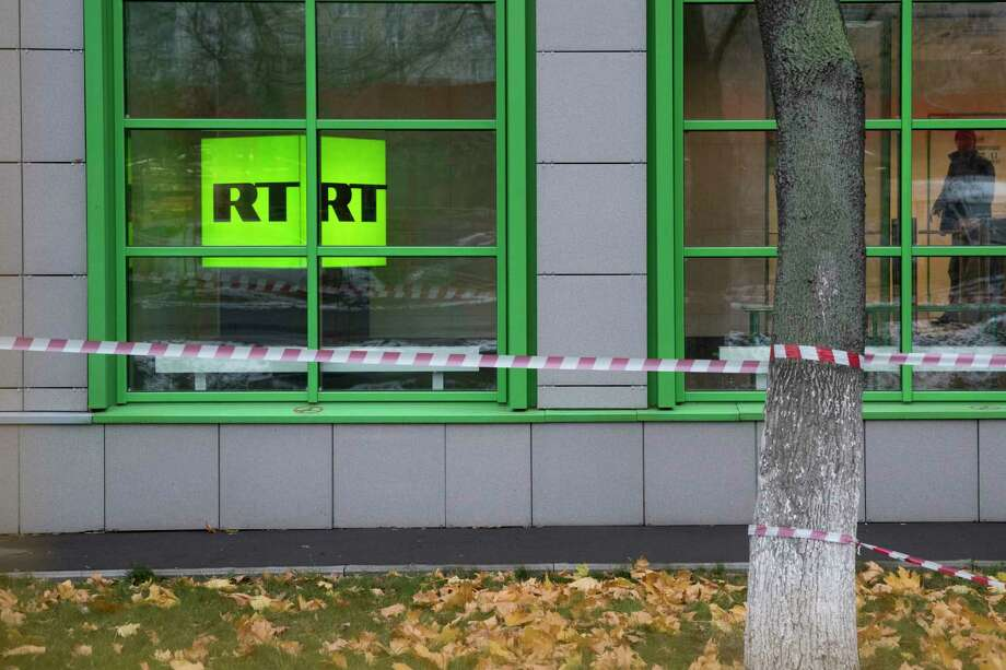FILE - In this Oct. 27, 2017, file photo, Russian state-owned television station RT logo is seen at the window of the company's office in Moscow, Russia. Russian state-funded TV channel RT has registered with the Justice Department as a foreign agent after pressure from the U.S. government, documents released Nov. 13, 2017, show. (AP Photo/Pavel Golovkin, File) Photo: Pavel Golovkin, STF / Copyright 2017 The Associated Press. All rights reserved.