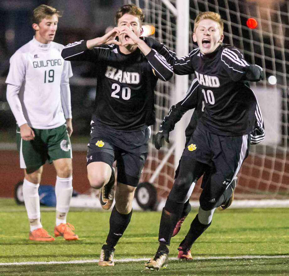 Hand's Owen McShane (20) and Scott Testori (10) celebrate after McShane's first-half goal in their Class L semifinal against Guilford on Monday. Photo: John Vanacore / For Hearst Connecticut Media / (c)John H.Vanacore/For Hearst Connecticut Media