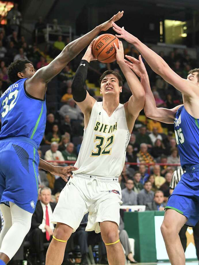 Siena's Evan Fisher drives to the basket against Florida Gulf Coast's Antravious Simmons, left, and Ricky Doyle during a basketball game at the Times Union Center on Monday, Nov. 13, 2017 in Albany, N.Y. (Lori Van Buren / Times Union) Photo: Lori Van Buren / 20041653A