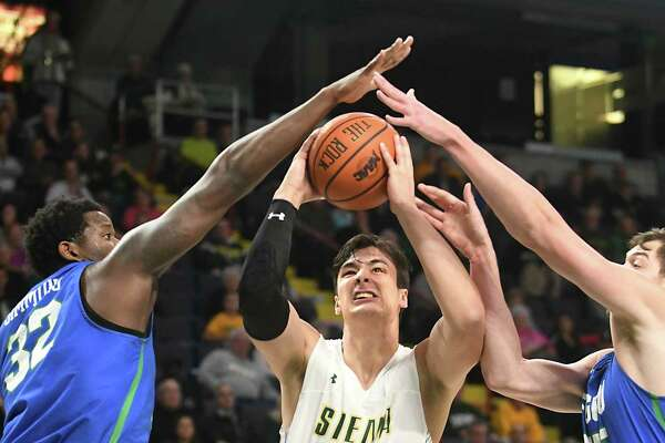 Siena's Evan Fisher drives to the basket against Florida Gulf Coast's Antravious Simmons, left, and Ricky Doyle during a basketball game at the Times Union Center on Monday, Nov. 13, 2017 in Albany, N.Y. (Lori Van Buren / Times Union)