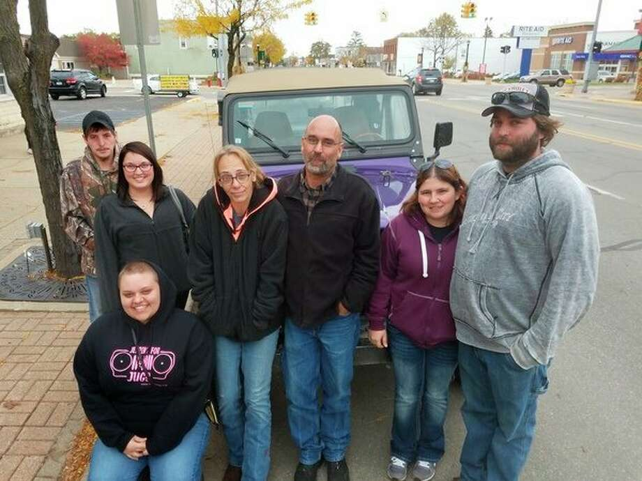 It's a Jeep family thing, from left, CJ Peterson, Kelsey Devlin, Alex Devlin (kneeling), Tammie Devlin, Todd Devlin, Holly Wood and Cody Devlin in front of Wood's Jeep that Cody Devlin helped build. (Photo by Tereasa Nims, for the Daily News)