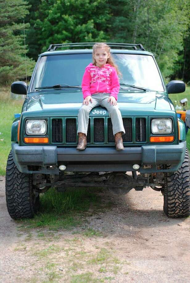 FILE — Serenity Porter finds a place on her dad, Chad Porter's Jeep during the 6th annual Jeep Creep in Gladwin. (Photo by Tereasa Nims, for the Daily News)