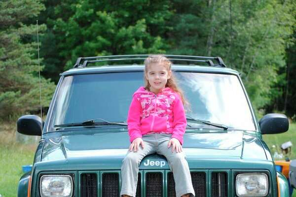 Serenity Porter finds a place on her dad, Chad Porter's Jeep during the 6th annual Jeep Creep in Gladwin. (Photo by Tereasa Nims, for the Daily News)