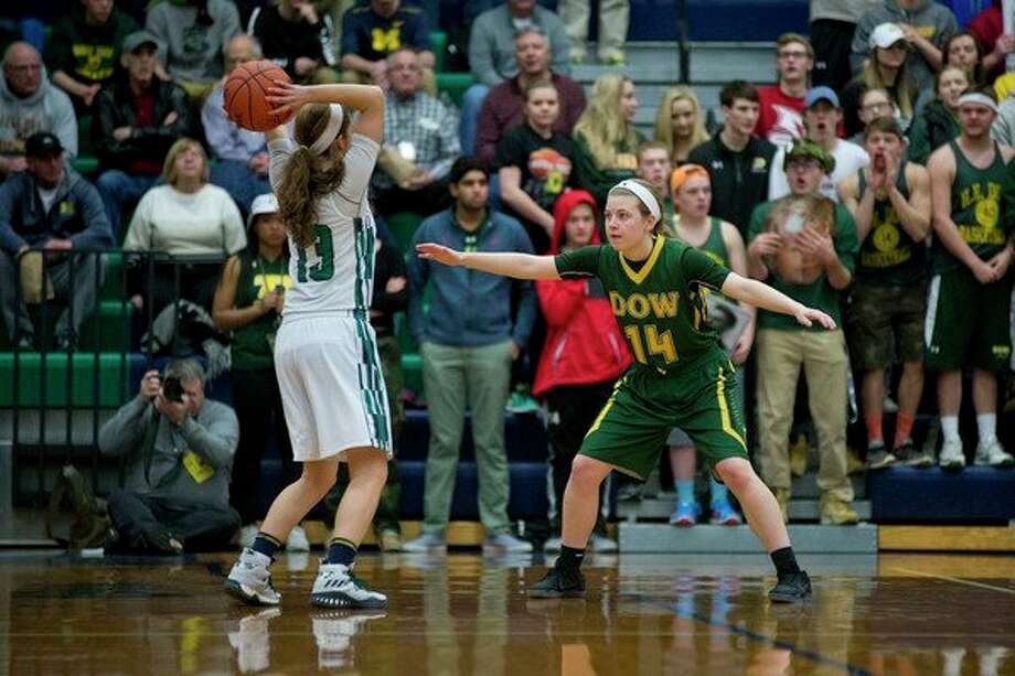 Dow High's Molly Davis, above right, will be counted on to lead a Chargers team that graduated a lot of talent and will be without injured guard Maizie Taylor for most of this season. Maddie Barrie, at left, will bea senior leader for Midland High girls' basketball season. (Midland Daily News file)