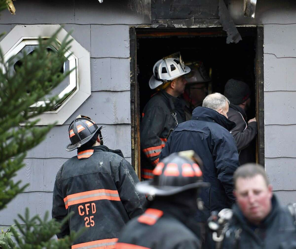 Firefighters work at the scene of a fire that damaged a home Tuesday morning, Nov. 14, 2017, in Cambridge.