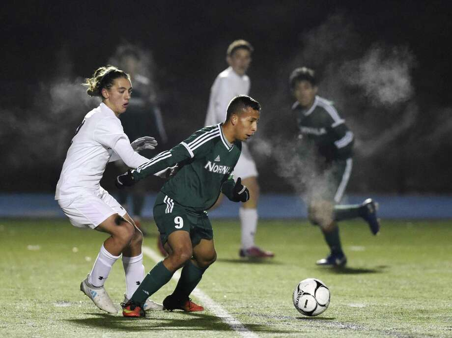 Naugatuck's Alexander Teixeira, left, defends Norwalk's Sebastian Echeverri as steam from the cold temperatures surrounds them in the high school boys soccer CIAC Class LL semifinal game between No. 1 Naugatuck and No. 20 Norwalk at Newtown High School in Newtown, Conn. Monday, Nov. 13, 2017. Photo: Tyler Sizemore / Hearst Connecticut Media / Greenwich Time