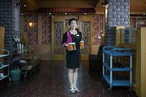 In a photo taken on September 26, 2017 wait staff Li Jin-Ju (23) poses for a portrait at the Arrirang bar and restaurant in Pyongyang. / AFP PHOTO / Ed JONES (Photo credit should read ED JONES/AFP/Getty Images)