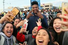 J.P. Morgan Corporate Challenge 5K volunteers take selfies with Golden State Warriors' rookie Jordan Bell in San Francisco, Calif., on Thursday, September 7, 2017.