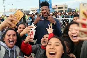 J.P. Morgan Corporate Challenge 5K volunteers take selfies with Golden State Warriors' rookie Jordan Bell in San Francisco, Calif., on Thursday, September 7, 2017.