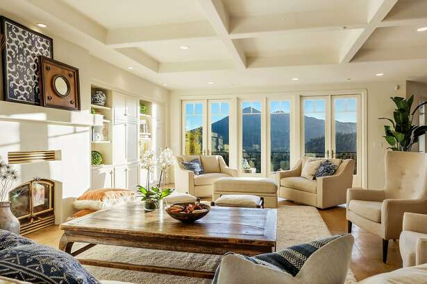 A coffered ceiling shelters a living room that includes a fireplace and built-ins.