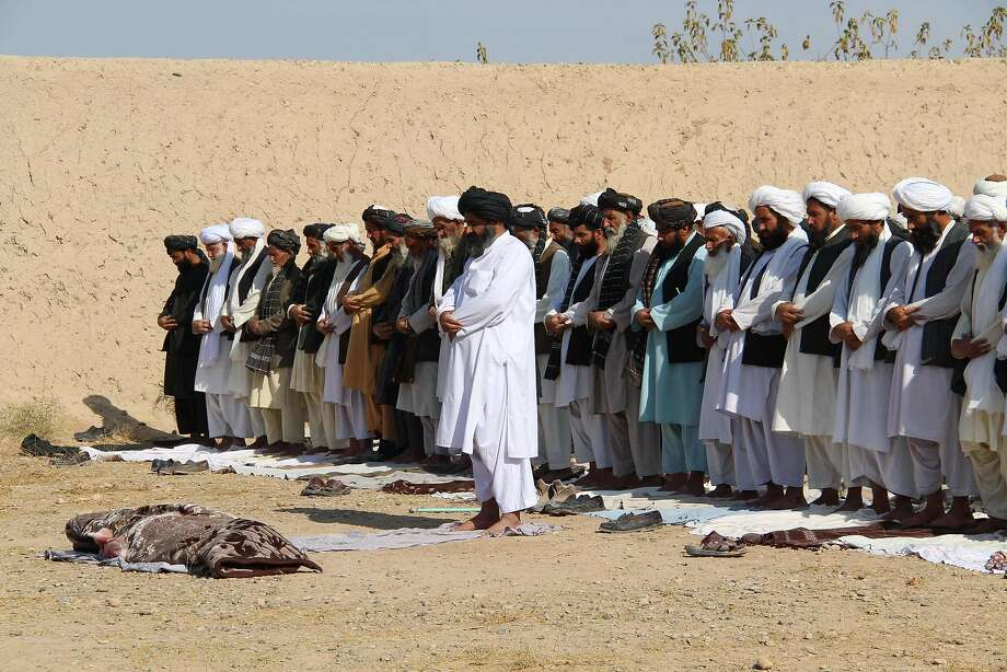 Afghan mourners pray in front of an Afghan police officer killed during a wave of Taliban attacks in Helmand province as insurgents step up assaults on the beleaguered security forces. Photo: NOOR MOHAMMAD, AFP/Getty Images