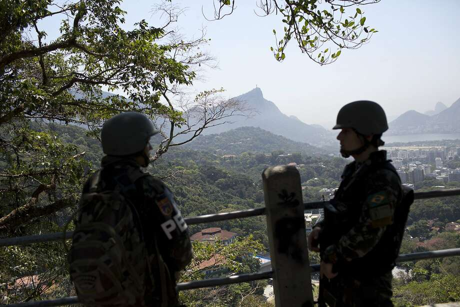 Soldiers stand guard in the Rocinha slum of Rio de Janeiro. Soaring violence in the city's hillside communities is rekindling a concern: Are Rio shantytowns safe to visit? Photo: Silvia Izquierdo, Associated Press