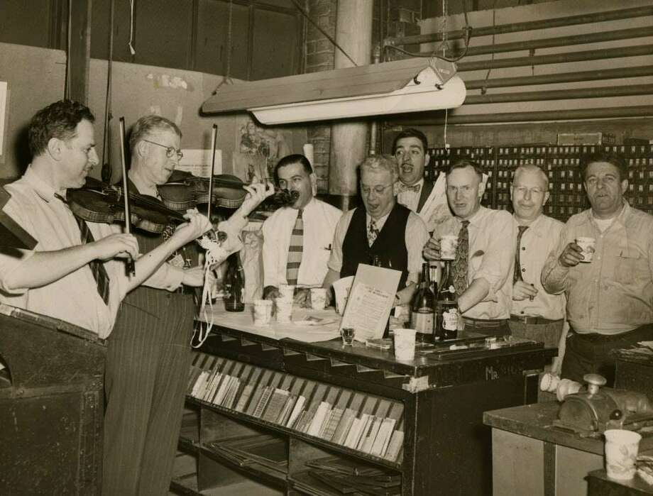 Workers at the Knickerbocker News are accompanied by two fiddlers while singing Christmas carols in a composing room, undated, Albany, N.Y