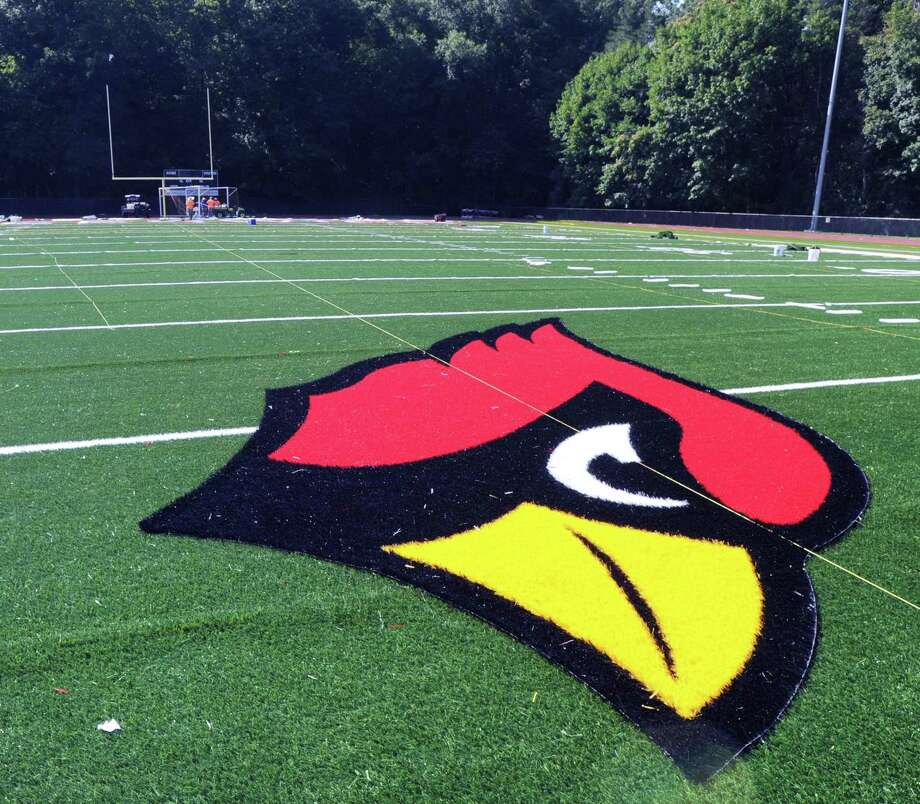 "The Greenwich High School Cardinal logo can be seen in the center of the field as workers from the Sprinturf Company headquartered in Atlanta, Ga., install the end zone lettering for the new artificial turf field at the high school's Cardinal Stadium, Conn., Wednesday afternoon, Aug. 24, 2016. Tim Karca, who was supervising and who was one of six workers who have been installing the field for the past three weeks said, "" We should be finished in a couple of days. It should be ready to be opened next Wednesday.""  Karca when asked what makes this turf field special responded ""The infill for the field is environmentally safe. It is also cooler because the sand coated plastic reflects heats."" Photo: Bob Luckey Jr. / Hearst Connecticut Media / Greenwich Time"