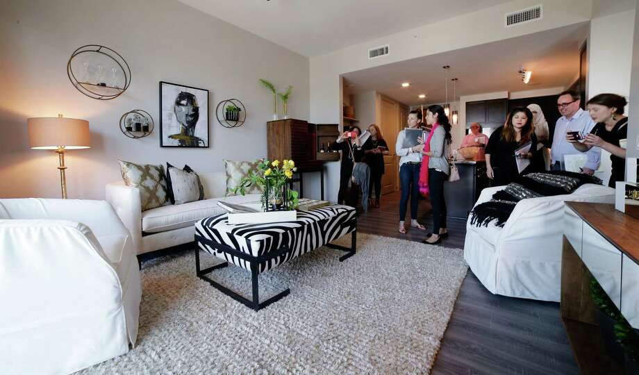 Tour attendants view the living area of a one bedroom residence on the 11th floor of the new Hotel ZaZa in Houston Nov. 14, 2017, in Houston, TX. (Michael Wyke / For the  Chronicle) Photo: Michael Wyke, For The Chronicle / © 2017 Houston Chronicle