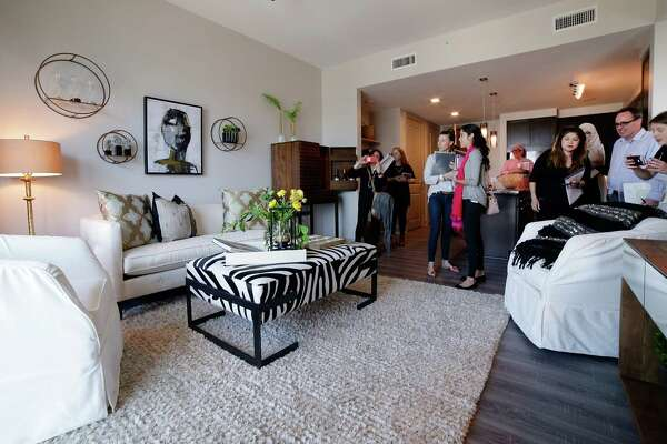 Tour attendants view the living area of a one bedroom residence on the 11th floor of the new Hotel ZaZa in Houston Nov. 14, 2017, in Houston, TX. (Michael Wyke / For the  Chronicle)