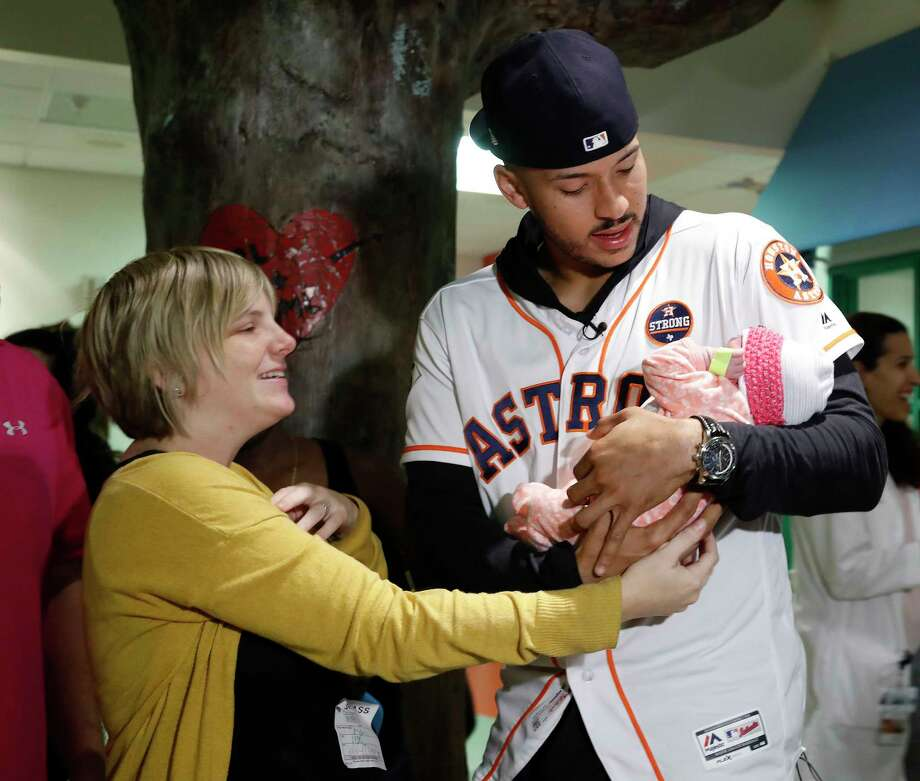 Houston Astro Carlos Correa holds twelve-day-old, Zoey Weinlein as her mother, Nicole hands her to him, as he visited patients at the Children's Memorial Hermann Hospital on Tuesday, Nov. 14, 2017, in Houston. Photo: Karen Warren, Houston Chronicle / © 2017 Houston Chronicle