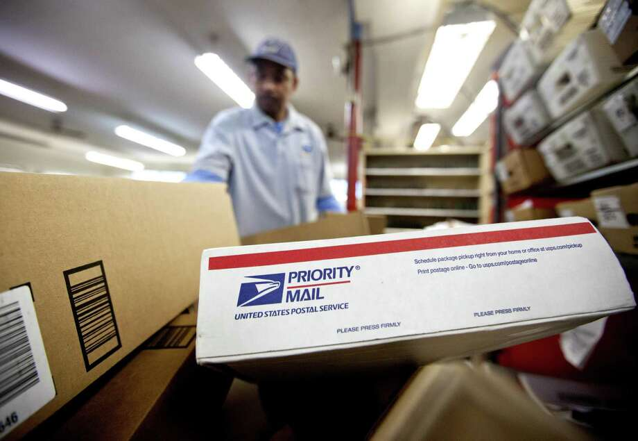 Packages wait to be sorted in a post office as a U.S. Postal Service letter carrier gathers mail to load into his truck before making his delivery run, in Atlanta. The Postal Service reported a loss of $2.7 billion for the fiscal year that ended Sept. 30. Photo: David Goldman /Associated Press / Copyright 2017 The Associated Press. All rights reserved.