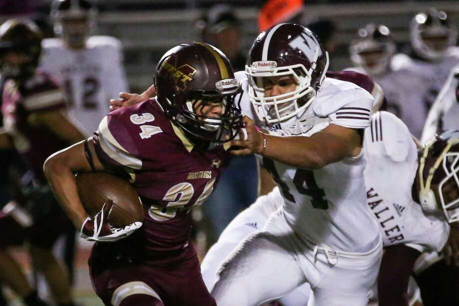 Magnolia West's Bryce Williamson (34) pushes off Waller's Chandler Crawford (44) while running the ball during the varsity football game on Friday, Oct. 27, 2017, at Mustang Stadium. (Michael Minasi / Houston Chronicle) Photo: Michael Minasi, Staff Photographer / © 2017 Houston Chronicle