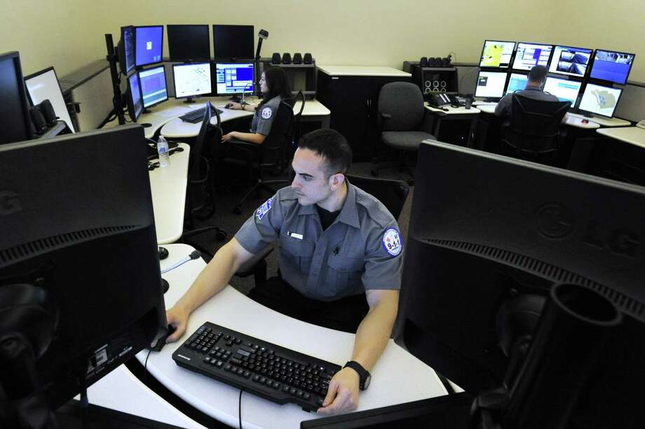 Derek Grisanti, foreground, is a telecommunicator in the Western Connecticut 911 Communications Center headquartered at the Danbury Police Station on Main Street in Danbury, Conn. Photo: Carol Kaliff / Carol Kaliff / The News-Times