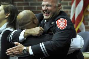 Deputy Chief Joe Halas gets a bear hug from his friend Danbury Police Det. Luis Ramos after Halas was sworn in as Deputy Chief of the Danbury Fire Department in a ceremony at City Hall Tuesday morning, Nov. 14, 2017.