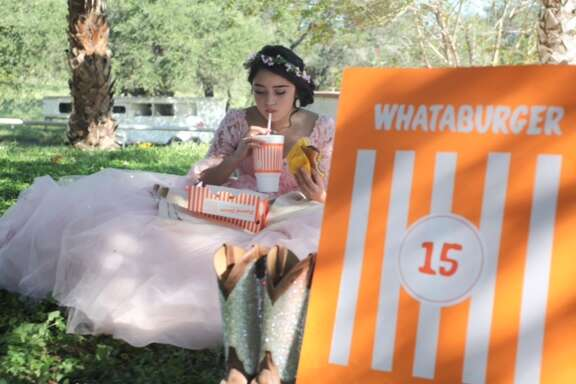 Evelyn Lopez Terrazas took birthday photos ahead of her quinceanera festivities in her quince ball gown and Texas accents, including cowgirl boots and, of course, Whataburger.