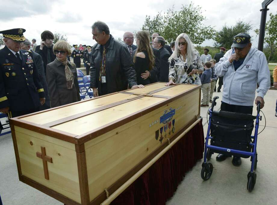 People pay their respects at the casket of Gen. Richard Cavazos, the Army's first Hispanic four-star General, at Fort Sam Houston National Cemetery on Tuesday, Nov. 14, 2017. Cavazos died on October 29 following a long illness. The casket was handmade by Ronnie Campsey, a Long Island restauranteur who served under Cavazos in Vietnam. It bears engravings of the medals Cavazos earned as a soldier, including two Distinguished Service Crosses, a Silver Star with Oak Leaf Cluster, Distinguished Flying Cross, the Bronze Star Medal with ÒVÓ device with four Oak Leaf Clusters, Purple Heart and Combat Infantry Badge. He retired in 1984 as the commanding general of U.S. Army Forces Command at Fort McPherson, Georgia. Prior to that, Cavazos commanded at every level of the Army, from platoon to Corps. A graduate of Texas Tech University's ROTC program, he served at Fort Hood on numerous occasions. Platoons from Fort Hood, Army North, Army South and the Army Medical Command were on hand for the burial. Photo: Billy Calzada, Staff