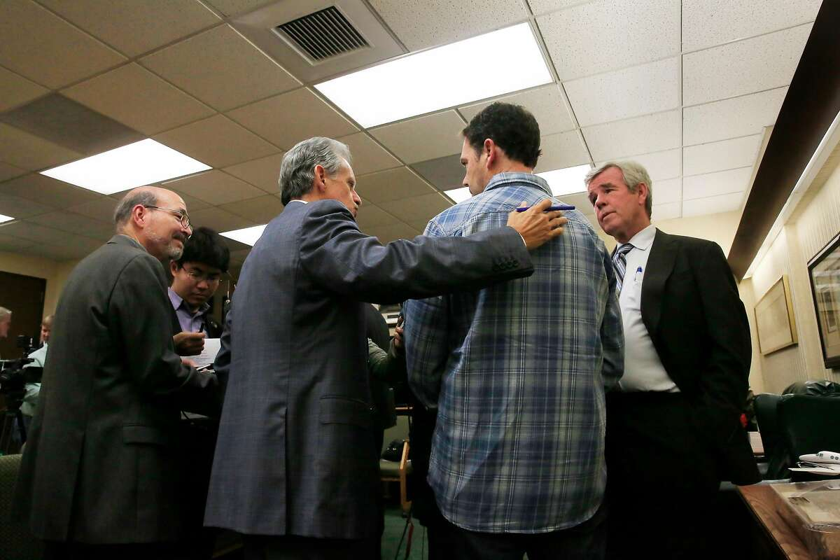 Frank Pitre (second from left), attorney Cotchett, Pitre & McCarthy, LLP, talks with Greg Wilson (second from right), Sonoma County resident who lost his home in the North Bay fires, as members of the media ask questions after a press conference at Cotchett, Pitre & McCarthy on Tuesday, November 14, 2017 in Burlingame, Calif.