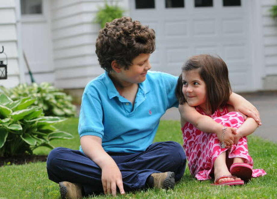 Ben Stowell, age 7, and his neighbor Aiva Geracitano, age 5, sit in front of her house in Latham on June 6, 2008. Aiva held a lemonade stand to raise money for Ben who was battling stage 4 metastatic osteosarcoma. (Lori Van Buren/Times Union archive)