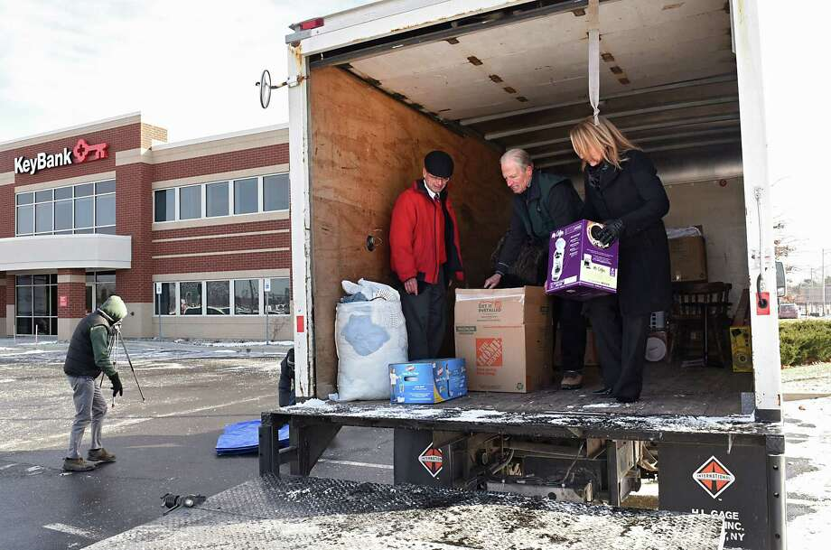 From left, Tom McGuire of Key Bank, Pete Newkirk of Homeless and Travelers Aid Society (HATAS) and Kelli Arnold of Key Bank move donations in the newly-purchased moving truck, just unveiled, to be used by the Capital Region Furniture Bank on Friday, Dec. 16, 2016 in Albany, N.Y. (Lori Van Buren / Times Union) Photo: Lori Van Buren / 20039133A