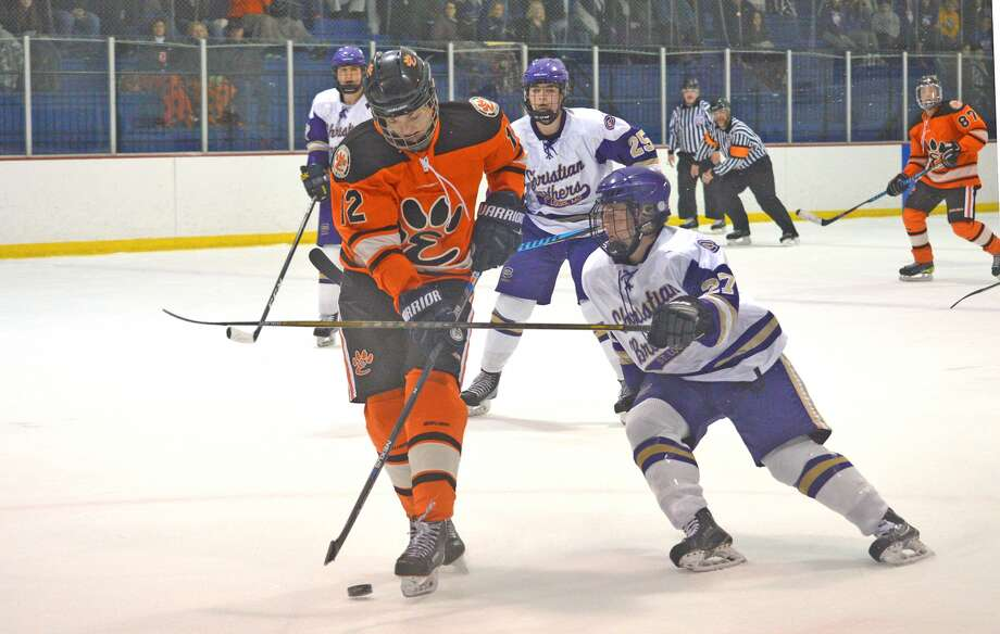 Edwardsville senior Stanley Lucas, left, tries to move the puck past a CBC defenseman during a regular-season game on Nov. 6 at Affton Ice Rink.