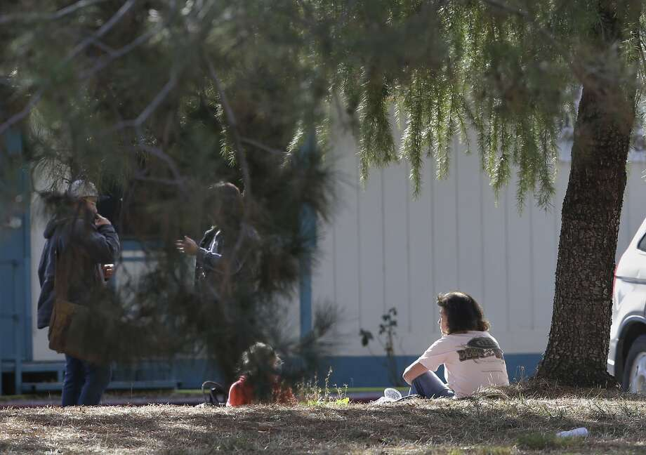 A woman and a child sit by an elementary school where a gunman opened fire in the community of Rancho Tehama Reserve in Corning, Calif., Tuesday, Nov. 14, 2017. The gunman choosing targets at random opened fire in the rural Northern California town Tuesday, killing several people at several sites and wounding others at the elementary school before police shot him dead, authorities said. (AP Photo/Rich Pedroncelli) Photo: Rich Pedroncelli, Associated Press